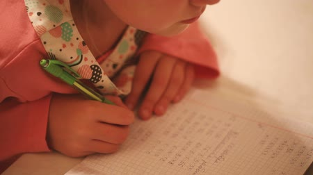 домашнее задание : Little girl is doing her homework close up. Стоковые видеозаписи