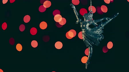 bugiganga : Keychain ballerina swinging on a chain on the background of beautiful christmas bokeh.