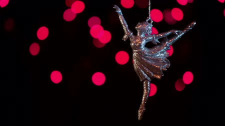ıvır zıvır : Keychain ballerina swinging on a chain on the background of beautiful christmas bokeh.