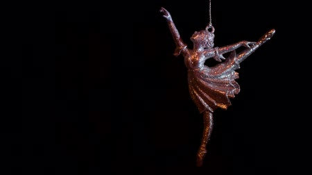 um objeto : Keychain ballerina swinging on a chain on the black background. Close up video.