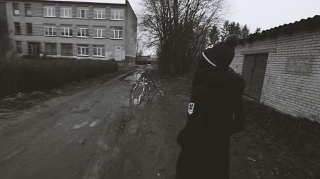 black dirt : Girl goes on a dirt road camera follows her. Black and white video.