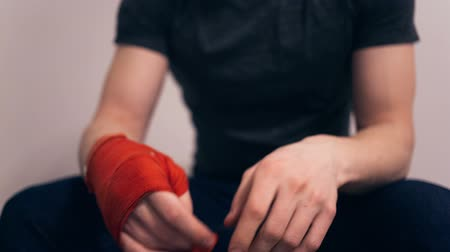 přadeno : Boxer after boxing removes a tape in which there was his hand. Close up video.