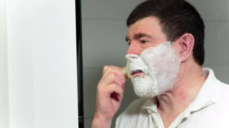 barbear : Man puts on a face cream by means of a small brush has a shave then. Video full hd.