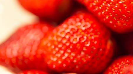 In a bowl with strawberries collect water. Close up video.