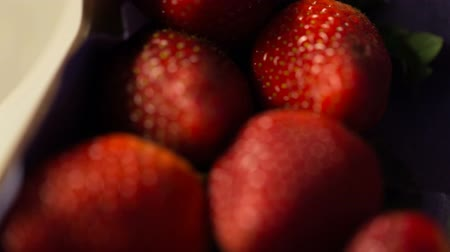 Camera shoots first strawberries in a box and then in bowl. Video full hd.