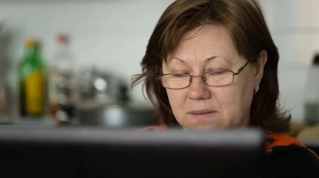 Middle aged woman in glasses looks at the screen and reads. Video full hd. 影像素材