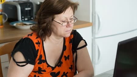 Middle aged woman in glasses using laptop. Video full hd.