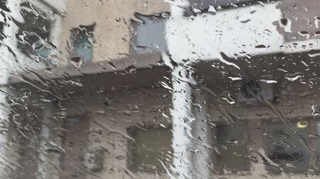 Rain drips on the glass in the background building. Waterdrops on a glass surface 影像素材
