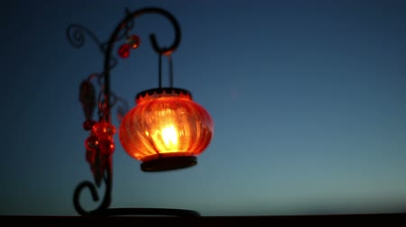 Red Lantern with a candle swaying in the wind at night Stock Footage