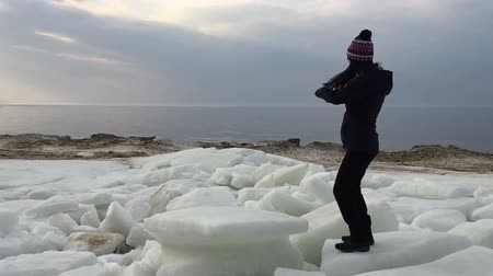 Girl beautifully dances near the gulf during the winter period. Slow motion video.