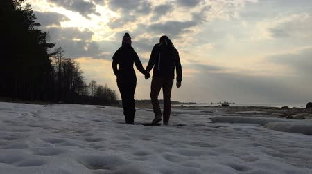 Young couple holding hands slowly walk during the winter period in the evening.