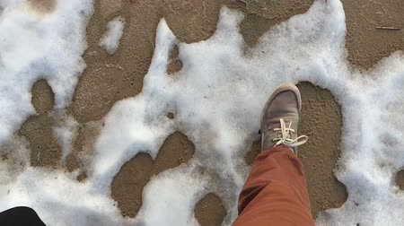 Two people walking on the garden snow. POV video.