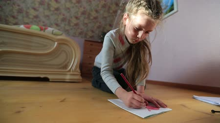 Little girl draws sitting on the floor. draws heart close-up