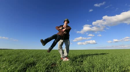 Father and his kid - daughter - playing together at a meadow, he is carrying her on his hands