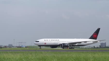 taxi : Toronto, OntarioCanada - June 2018 - An Air Canada B777 in 2018 livery taxis at Toronto with the terminals in the BG Stock Footage