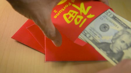 bao : Putting dollar bills inside a red envelope or hong bao in Chinese New year