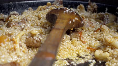 szépia : Cooking spanish paella, Stiring rice Stock mozgókép