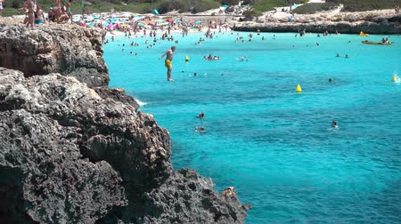 baleár : Tourist jumping over the cliff to the turquoise sea water in cala Bosch, Menorca, Spain.