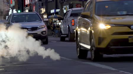 poluir : Manhattan street scene with steam coming from manhole cover