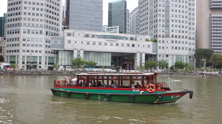 SINGAPORE- OCT 13, 2017: Tourist boat travel along Singapore River Places in Singapore. The Singapore River Cruise is one of the main tourist attractions in this former British colony.