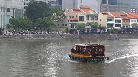SINGAPORE - OCTOBER 23 2017: Beautiful view of Boat Quey and traditional wooden tourist boat sailing along the Singapore River with azure water. Dostupné videozáznamy