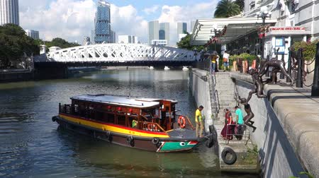 SINGAPORE - DECEMBER 02 2017: A tourist boat docking at Boat Quay in Singapore. Singapore is global financial center with a tropical climate and multicultural population.