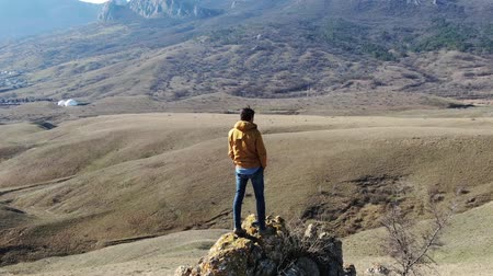admires : man in casual clothes standing on a rock and admires a mountain autumn landscape Stock Footage