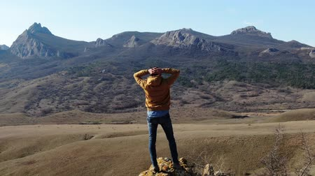 standlar : a man stands on a rock and admires the mountain autumn landscape