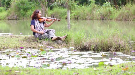 undershirt : an asian woman with black hair, jean and scarf plays violin near the lake and lotus pool