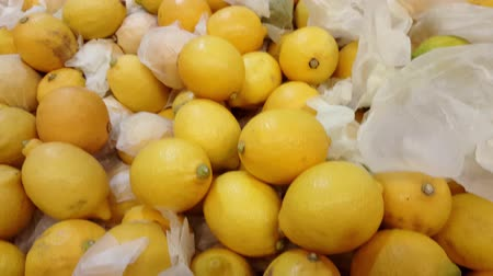 limão : Pile of soft yellow lemons in a market, pan motion