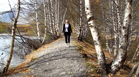 wooden path : Young happy woman is jumping on the track and in the woods of birch