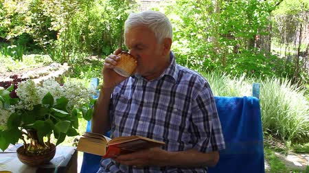 ağarmış : An elderly man sitting and reading a book and drinking juice in outdoor garden Stok Video