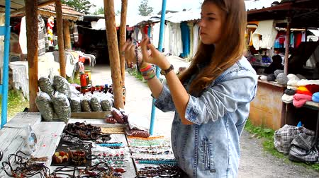 possession : Young girl on the market chooses and tries beads and pendants