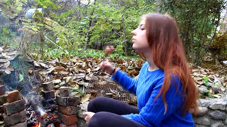 günlüğü : Young girl fry sausage on a fire outdoors and eat it Stok Video