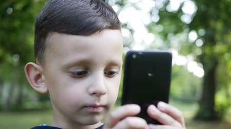 photograph : little boy taking photo with his smartphone in the park slow motion