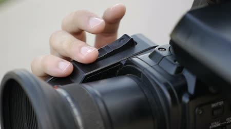 mirror less camera : filmmaker clicks the zoom buttons in professional tv camera Stock Footage