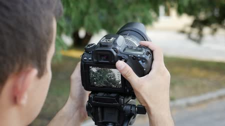 mirror less camera : filmmaker takes video with DSLR Camera Stock Footage