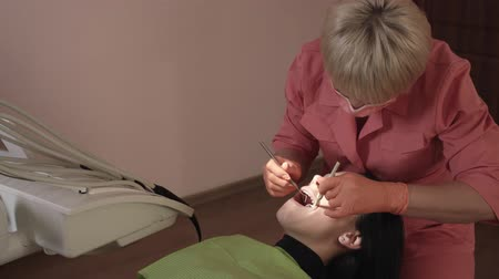 медицинская помощь : Dentist Examines And Heals The Teeth Of A Young Woman. Dentist Using Tools, Equipment And Instruments In The Dental Office.