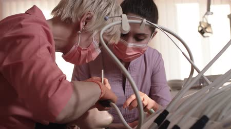 лечит : Dentist Examines And Heals The Teeth Of A Young Woman. Dentist Using Tools, Equipment And Instruments In The Dental Office.