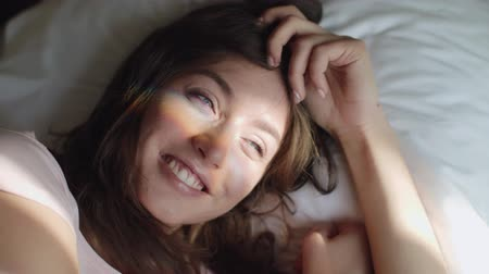 Young Beautiful Woman Wakes Up In The Morning. Sun Rays Fall On Her Face. Close Up.