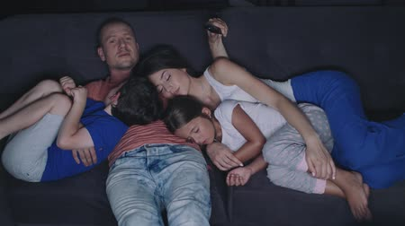 кондоминиум : Parents And Their Children Are Watching TV. They Sit On A Sofa In Their Cozy Living Room. Its Evening. Children With Their Mother Fell Asleep.
