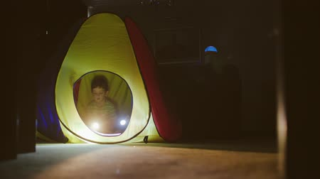 Happy Little Girl And Boy Play In A Tent. Rays Of Flashlights.