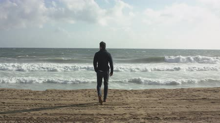 Man Looks At The Waves At Sea. Man Walking On Ocean Beach.