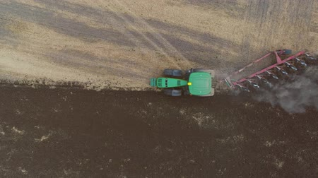 Aerial View Of A Big Field. Tractor Plows A Big Field. Storks Walk Around The Tractor In The Field.