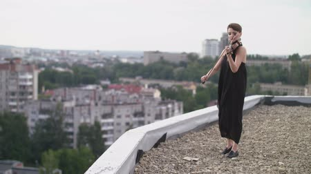 podfuk : Woman In Evening Dress Playing The Violin On. Beautiful Young Woman On The Roof Of The Building. Dostupné videozáznamy