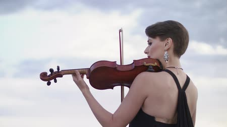 gracefully : Woman In Evening Dress Playing The Violin On. Beautiful Young Woman On The Roof Of The Building. Stock Footage
