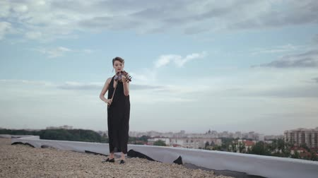 elite : Woman In Evening Dress Playing The Violin On. Beautiful Young Woman On The Roof Of The Building. Stock Footage