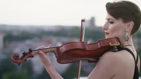 seçkinler : Woman In Evening Dress Playing The Violin On. Beautiful Young Woman On The Roof Of The Building. Stok Video