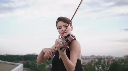 houslista : Woman In Evening Dress Playing The Violin On. Beautiful Young Woman On The Roof Of The Building. Dostupné videozáznamy