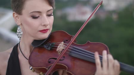 элита : Woman In Evening Dress Playing The Violin On. Beautiful Young Woman On The Roof Of The Building. Стоковые видеозаписи